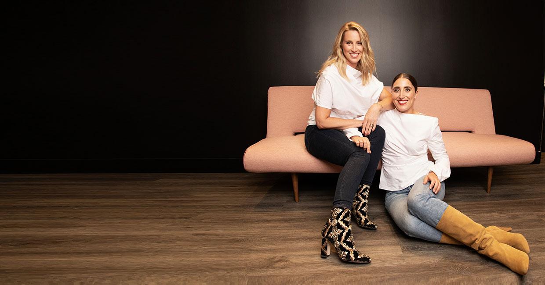 Catherine Hébert et Ryma Brixi, stylistes personnelles, souriantes, assises sur un sofa rose sur plancher de bois et devant un mur noir