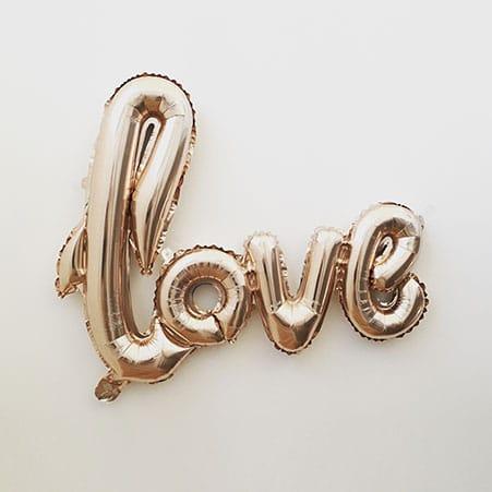 Mot love en ballons gonflés à l'hélium de couleur doré sur fond blanc