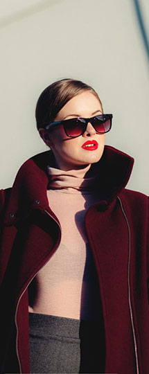 Femme professionnelle avec lunettes de soleil, manteau rouge vin ouvert sur un chandail col roulé rose