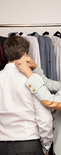 homme de dos avec chemisier blanc, styliste faisant des ajustements au collet de la chemise