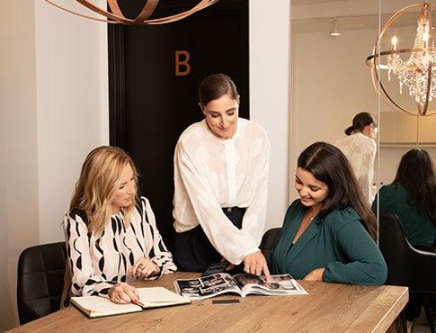 2 femmes assises à une grande table de bois regardant des éléments leur étant pointés dans un magazine par une styliste personnelle debout entre elles.