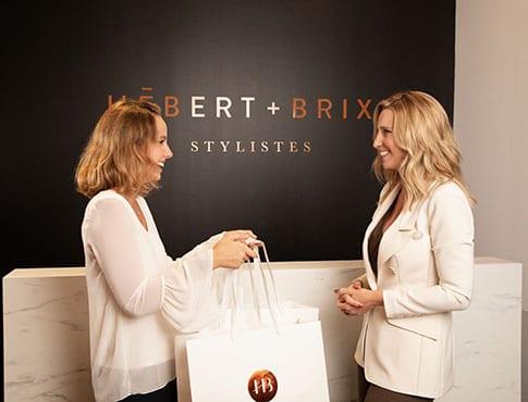 femme blonde avec chemisier blanc tendant 2 sacs de magasinage Hébert + Brixi à une femme blonde vêtue d'un veston blanc devant mur noir et comptoir de marbre blanc