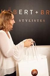 femme blonde avec chemisier blanc tenant un sac de magasinage Hébert + Brixi devant mur noir
