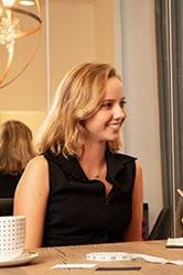 jeune femme blonde souriante assise à une table