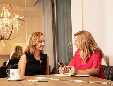 femme souriante vêtue d'un chemisier noir assise à une table de bois discutant avec sa styliste personnelle qui prend des notes dans un cahier