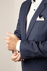 Torse d'un homme en complet bleu marin avec chemisier blanc, qui ajuste ses poignets de chemise