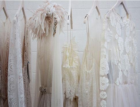 tenues de soirée dans les teintes de blanc sur des cintres blancs sur un mur de briques blanches