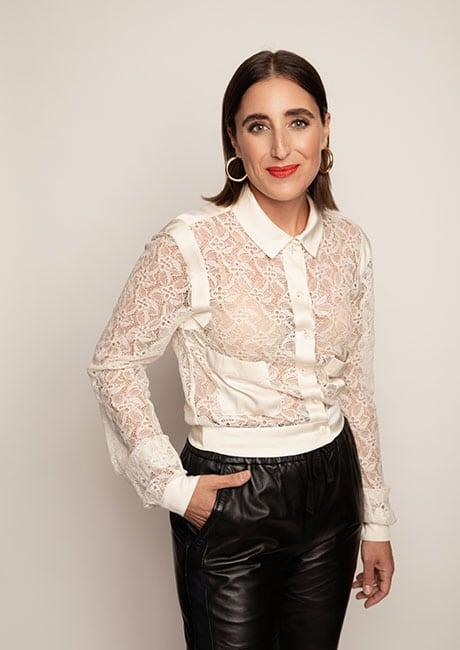 Portrait de Ryma Brixi souriante vêtue d'un chemisier blanc en dentelle et d'un pantalon de cuir noir