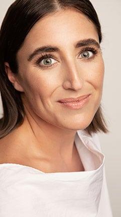 Portrait en gros plan de Ryma Brixi, souriante vêtue d'un haut blanc